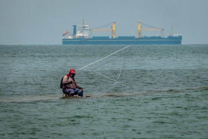 Memancing ikan di atas struktur dam pemecah gelombang