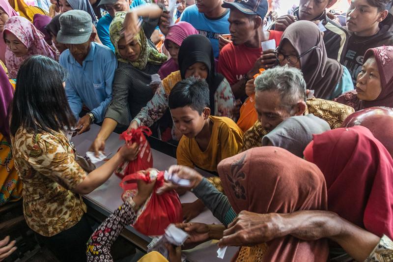 Warga mengantre untuk mendapatkan paket sembako gratis saat digelarnya Pasar Murah Ramadan di Mranggen, Demak, Kamis (24/5/2018). (ANTARA FOTO/Aji Styawan)