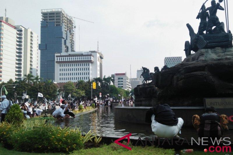 Massa aksi berwudhu di kolam Patung Arjuna Wiwaha untuk shalat