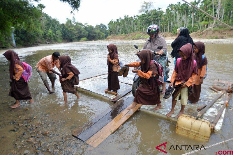 Akibat jembatan ambruk, warga desa Siro menggunakan rakit untuk menyeberang