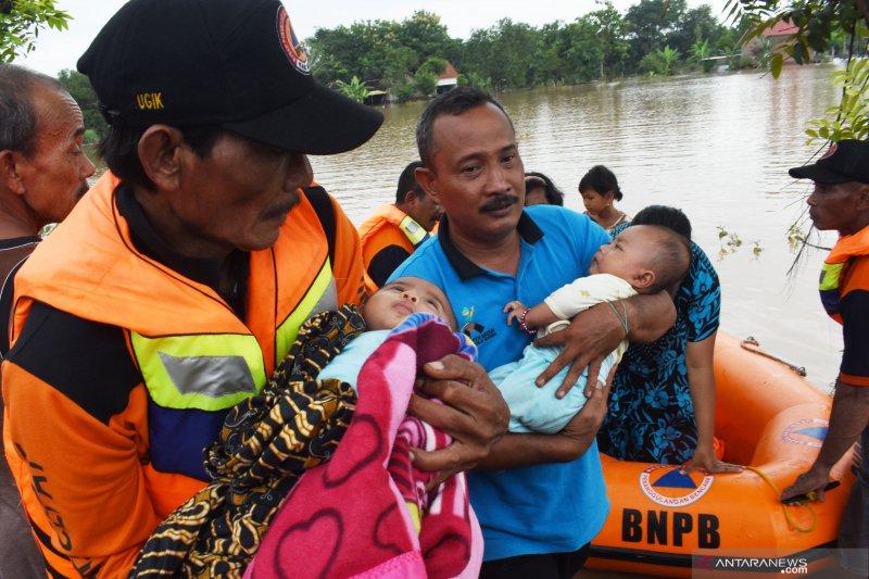 Relawan Badan Penanggulangan Bencana Daerah (BPBD) mengevakuasi dua balita  saat terjadi banjir di Desa Kedungrejo ac8f4a3f62