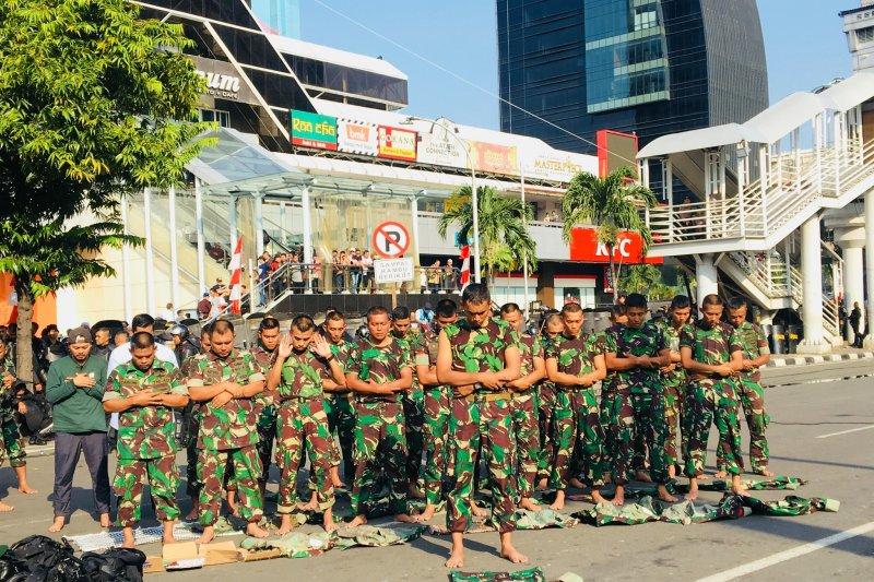 Anggota TNI Shalat Ashar berjamaah di depan Gedung Bawaslu RI