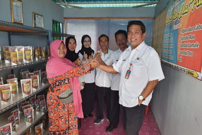 Kadis KP Sulteng Hasanuddin Atjo (kanan) bersalaman dengan salah seorang korban bencana Palu yang mengembangkan usaha olahan hasil perikanan di Huntara Kelurahan Lere, Kota Palu, Rabu (10/7). (Antaranews Sulteng/Dokumen DKP Sulteng)