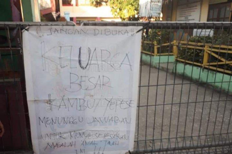 Warga menggembok pintu masuk SD Inpres Perumnas I Waena dalam aksi protes
