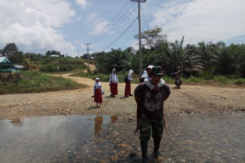 Prajurit TNI ini gendong anak sekolah menyebrangi Sungai