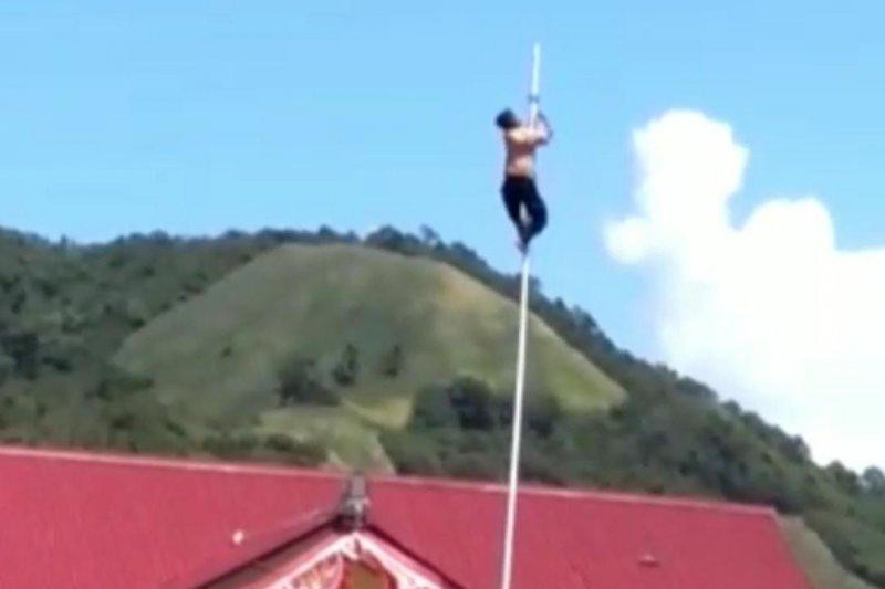 Joni panjat tiang untuk menyelamatkan tali bendera yang putus