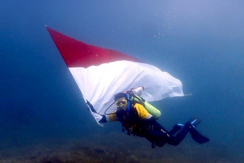 Amman Mineral kibarkan bendera dan pasang terumbu karang di bawah laut
