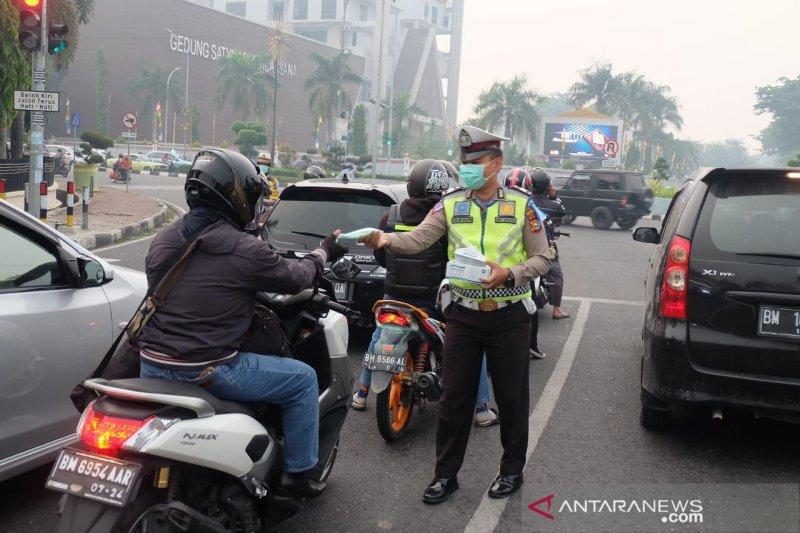 Karhutla Riau - Polisi lalu lintas Pekanbaru kembali bagikan masker pengendara motor terdampak asap