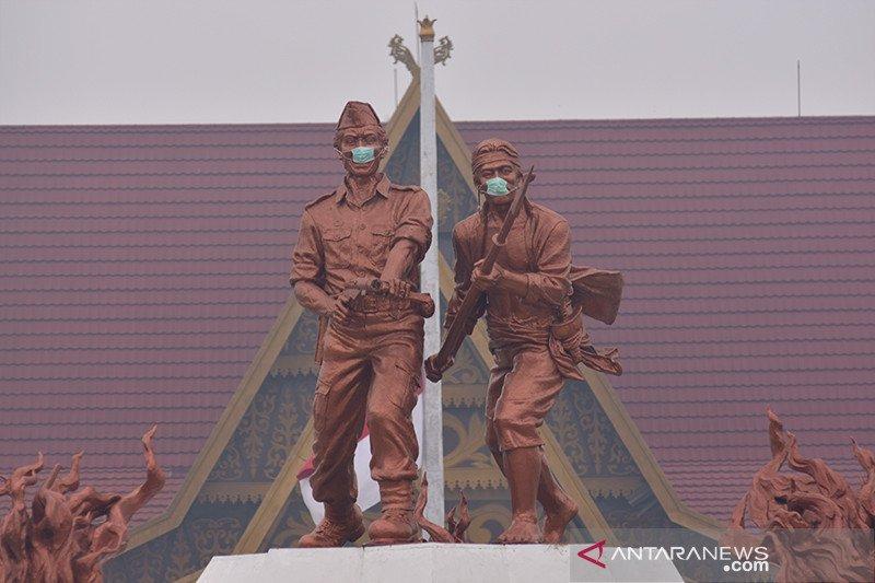 Patung Tugu Api pun dipasangi masker saat pekatnya kabut asap