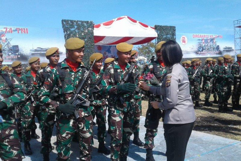 Pemberian bunga dari Polwan kepada prajurit warna HUT TNI di Manado