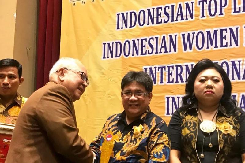 Ketua KPU Manado, Sunday Rompas, terima Indonesian Top Leadership Achievement 2019