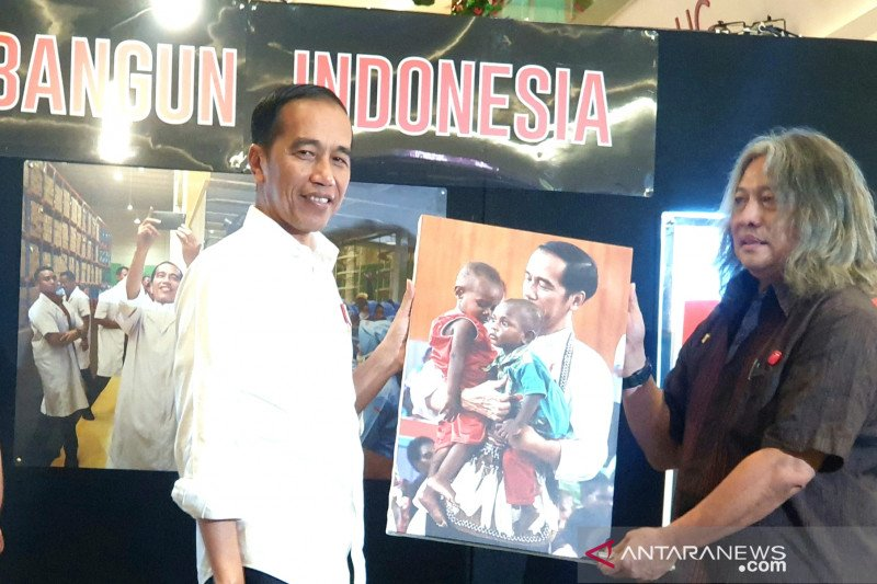 Jokowi enchanted by his photo holding two native  Papuan kids