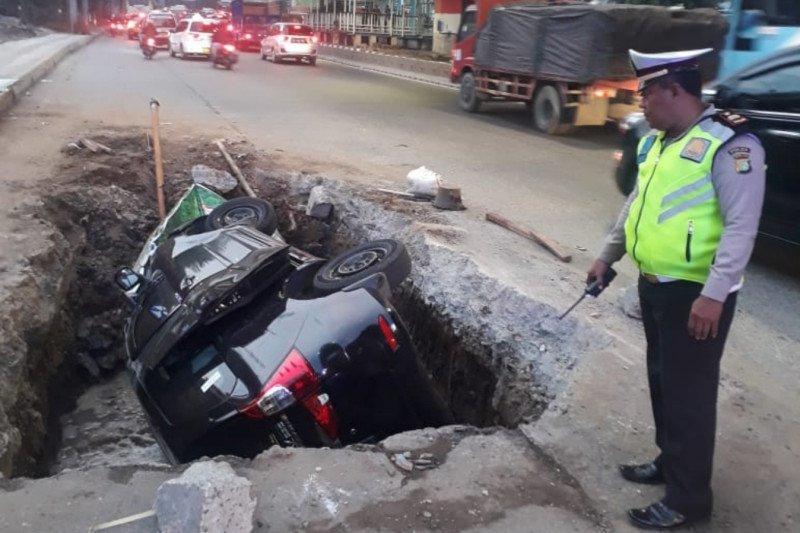 Tak hati-hati, mobil pribadi dan pengendaranya terperosok lubang galian jalan