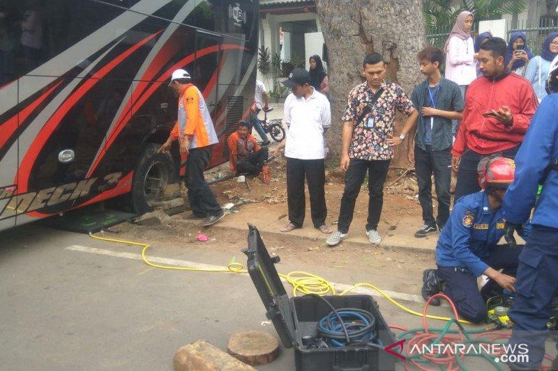 Bus pariwisata terperosok di saluran air Jalan Matraman