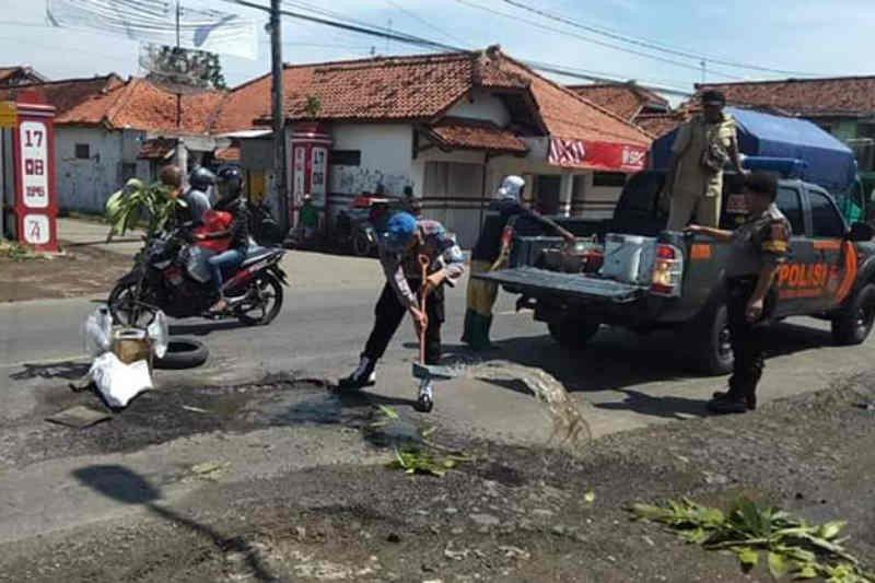 Polisi dan warga Majalengka tambal jalan berlubang