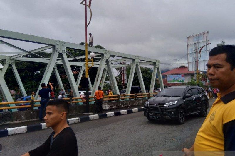 Seorang pria tak dikenal panjat jembatan Andalas Padang