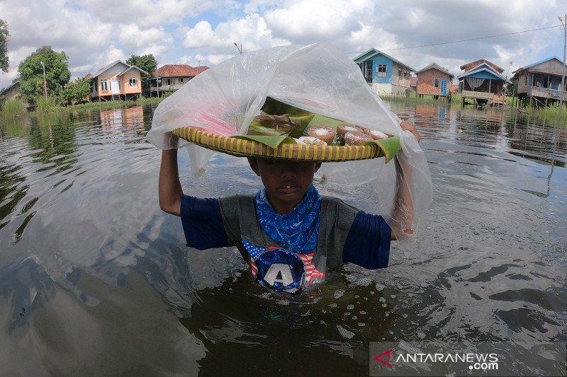 Tetap berjualan di tengah banjir