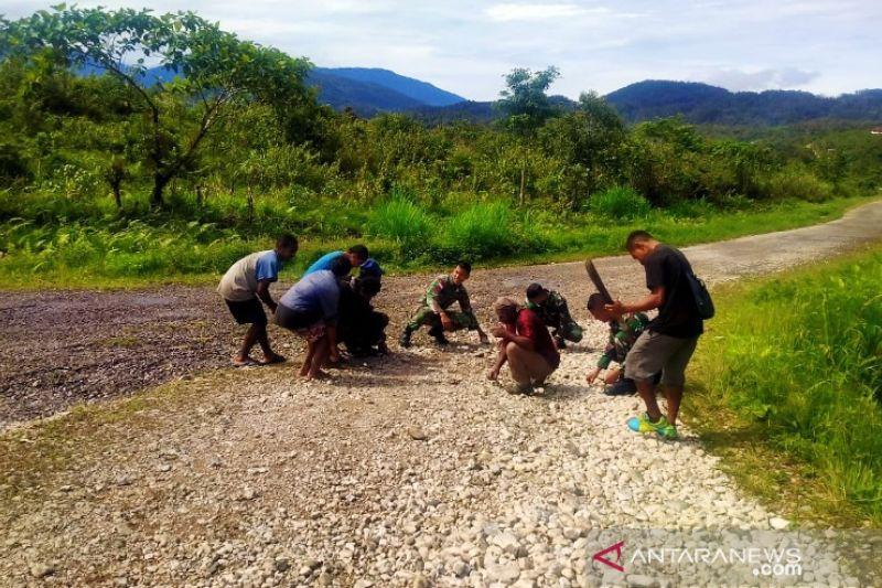 Satgas TNI bersama warga Kutdoi Oksibil membersihkan jalan Trans Papua