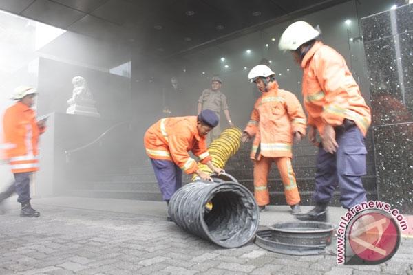 Petugas kebakaran membereskan kembali peralatan pemadam kebakaran