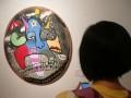 """Seorang pengunjung menikmati sebuah lukisan bulat karya AmyZahrawan pada pameran seni rupa """"Project Hybrid -Little Box"""", di Bentara Budayam Jakarta, Kamis malam (19/1). Pameran ini akan berlangsung hingga 30 Januari 2012. (FOTO ANTARA/Dodo Karundeng)"""