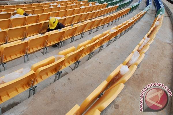 Pekerja menyelesaikan pemasangan ratusan kursi tempat duduk penonton
