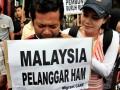 Puluhan aktivis buruh dari Migrant Care menggelar aksi di depan Kantor Kedutaan Besar Malaysia, Jalan Rasuna Said, Jakarta, Selasa (1/5). Mereka mengecam keras kriminalisasi dan tindakan represif yang dilakukan oleh aparat Malaysia dengan melakukan penembakan tiga TKI asal Nusa Tenggara Barat (NTB), yakni Abdul Qodir Jaelani, Mad Noor dan Herman pada 24 Maret 2012 lalu. FOTO ANTARA/Dhoni Setiawan/Koz/pd/12.