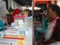Seorang ibu mengambil obat usai melakukan pengecekan kesehatan oleh petugas medis di Posyandu Lansia di Halaman Kantor Pos Abepura, Jayapura, Papua, Jumat (4/5). Posyandu Lansia dan pengobatan gratis bagi masyarakat usia lanjut ini dilaksanakan oleh Puskesmas Waena bekerjasama dengan Bank Mandiri dan Kantor Pos wilayah Sumapua yang bertujuan untuk memeratakan pelayanan kesehatan gratis bagi seluruh masyarakat. (FOTO ANTARA/Anang Budiono)