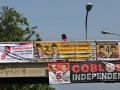 Pejalan kaki melintas di jembatan penyeberangan orang (JPO) yang telah dipasangi spanduk sejumlah dukungan calon gubernur DKI di kawasan Jalan Otto Iskandardinata, Jakarta, Senin (2/7). Spanduk yang memuat dukungan terhadap calon gubernur dan wakil gubernur DKI banyak dijumpai di beberapa tempat umum di Jakarta walaupun petugas telah menertibkan keberadaaan poster dan spanduk tersebut sebelum masa kampanye. (FOTO ANTARA/Reno Esnir)
