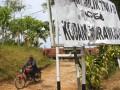 Seorang warga melintas di depan papan tanda kepemilikan tanah yang rusak di lokasi bentrokan sengketa tanah di Desa Hargokuncaran, Malang, Jawa Timur, Sabtu (7/7). Sebanyak 8 orang terluka akibat bentrokan antara TNI dan warga menyusul sengketa lahan seluas 662 hektare tersebut. (FOTO ANTARA/Ari Bowo Sucipto)