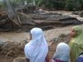 Warga menyaksikan jembatan yang rusak berat akibat diterjang banjir bandang di Kelurahan Koto Panjang, Kec. Pauh, Padang, Sumbar, Rabu (25/7). Banjir bandang yang merendam puluhan rumah di sejumlah kelurahan di Lima Kecamatan, di Padang itu, membuat ratusan warga terpaksa mengungsi, sejumlah rumah dilaporkan rusak berat dan hanyut terbawa air. (ANTARA/Iggoy el Fitra)