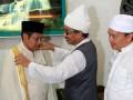 Pemimpin pondok pesantren Al-Kautsar Al-Akbar Buya Syekh Ali Akbar Marbun (kedua kanan) memakaikan jubah kepada Ketua Umum DPP Partai Demokrat (PD) Anas Urbaningrum (kiri) disaksikan Wasekjen PD Ramadhan Pohan (kanan) ketika bersilaturahmi ke ponpes Al-Kautsar Al-Akbar di Medan, Sumatera Utara, Rabu (25/7). Dalam silaturahmi tersebut, Anas didampingi sejumlah anggota DPR Fraksi PD seperti Ramadhan Pohan dan Sutan Batoeghana, serta pengurus DPD PD Sumatera Utara. (FOTO ANTARA/Ridhwan Ermalamora/HO)
