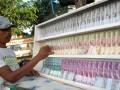 Penjual jasa penukaran uang menunggui uang baru di depan Masjid Baitul Hakim Kota Madiun, Jatim, Selasa (24/7). Penjual jasa memungut tambahan 10 persen dari jumlah uang yang ditukarkan, misalnya setiap Rp 100 ribu akan dikenai tambahan Rp 10 ribu, dan menyediakan uang pecahan Rp 2 ribu, Rp 5 ribu, Rp 10 ribu dan Rp 20 ribu. (FOTO ANTARA/Siswowidodo)