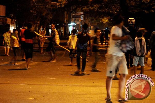 Sejumlah remaja membawa kayu dan batu ketika terjadi tawuran di depan