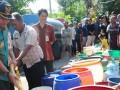 Walikota Tegal, Ikmal Jaya mengisi air saat pembagian air bersih di Kelurahan Kalinyamat Kulon, Tegal, Jateng, Rabu (1/8). Pada musim kemarau saat ini, dua kelurahan di daerah tersebut mengalami krisis air bersih terutama untuk kebutuhan mandi, masak dan mencuci. (ANTARA/Oky Lukmansyah)