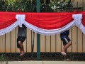 Dua orang pekerja memasang atribut merah putih di Jalan Tanah Abang, Jakarta, Minggu (12/8). Sejumlah kantor dan instansi pemerintahan mulai memasang atribut kemerdekaan untuk memperingati HUT RI ke 67 pada 17 Agustus mendatang. (ANTARA/Dian Dwi Saputra)