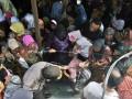 Seorang anggota polisi membantu keluar seorang warga yang terhimpit saat mengantre paket sembako yang dibagikan oleh Pengajian Majelis Taklim Jabar Noor di Jalan Ngalengko Medan, Sumut, Selasa (14/8). Sebanyak 7.000 paket sembako berupa beras, minyak goreng, mie instan dan uang Rp 30 ribu dibagikan kepada warga setempat dalam rangka menyambut Hari Raya Idul Fitri 1433 H. FOTO ANTARA/Septianda Perdana/Koz/pras/12.