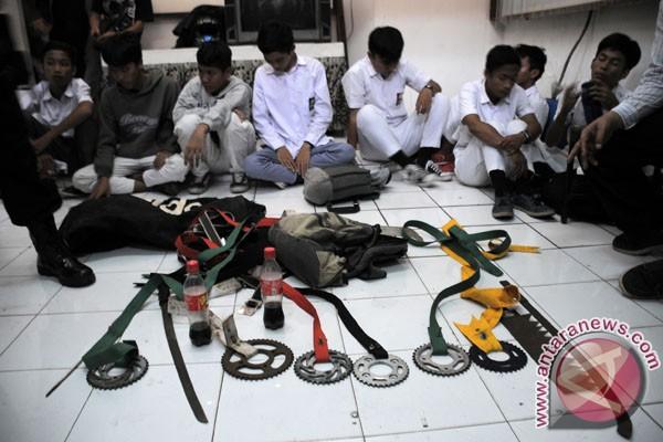 Polisi memperlihatkan barang bukti senjata tajam yang disita dari ...
