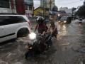 Anak-anak membantu kendaraan melintasi di genangan air hujan yang membanjiri jalan di depan gedung RS Mintoharjo, Benhil, Jakarta Pusat, Sabtu (22/12). Hujan lebat kembali melanda ibukota dan menyebabkan genangan air di sejumlah sudut.  ANTARA/Fanny Octavianus