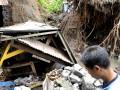 Seorang warga melihat bangunan Pura yang terkena tanah longsor dan pohon tumbang yang disebabkan cuaca buruk di Denpasar, Bali, Selasa (8/1). Sejak Senin (7/1) sebagian besar wilayah Pulau Bali diguyur hujan disertai angin kencang sehingga mengakibatkan beberapa kawasan permukiman tergenang, longsor, pohon tumbang dan pemadaman listrik. (ANTARA/Nyoman Budhiana)