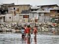 Beberapa anak melintas di dekat bangunan liar yang terendam air di daerah Waduk Pluit, Jakarta Utara, Kamis (24/1). Pemerintah Provinsi DKI Jakarta telah menyiapakan anggaran sebesar 1 triliun rupiah untuk menormalisasi Waduk Pluit, karena kedalaman saat ini hanya 2-3 meter karena endapan lumpur dan sampah, serta menyempit karena banyak bangunan liar di sekitar waduk. (FOTO ANTARA/Yudhi Mahatma)