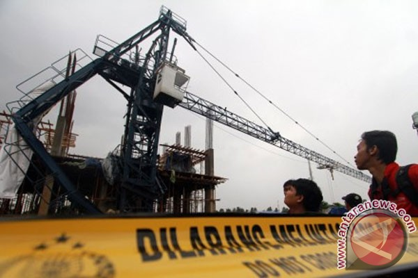 Sejumlah warga melihat dari dekat sebuah tower crane yang ambruk di