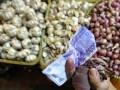 Pembeli bawang memegang uangnya saat berbelanja di Pasar Senen, Jakarta Pusat, Rabu (13/3). Asosiasi Pedagang Pasar Indonesia menilai naiknya harga bawang putih dan bawang merah dalam sepekan terakhir terkait dengan ketidakberesan kebijakan impor sektor pangan. (FOTO ANTARA/Fanny Octavianus)