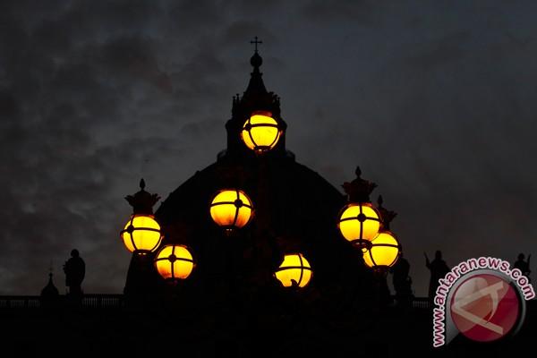 Lampu-lampu menghiasi Lapangan Santo Petrus, dengan latar be