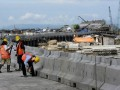 Tiga pekerja menyelesaikan pekerjaan tahap akhir jalan tol penghubung Bandara Ngurah Rai-Nusa Dua di Denpasar, Jumat (12/4). Jalan bebas hambatan sepanjang 12,1 Km di atas laut itu ditargetkan dapat diuji kelaikan pada Mei 2013 sehingga menjelang KTT APEC jalan tersebut sudah dapat beroperasi untuk memperlancar kegiatan itu. (FOTO ANTARA/Nyoman Budhiana)