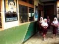 Sejumlah murid SD Negeri Lopangdomba, Kota Serang, Banten melintas di lorong kelas mereka yang terendam banjir dan berlumpur usai mengikuti apel Peringatan Hari Pendidikan Nasional, Kamis (2/5). Meski Pemda setempat sudah diinstruksikan Mendiknas untuk memperbaiki drainase guna mengatasi banjir namun hingga saat ini tidak ada realisasinya. (ANTARA/Asep Fathulrahman)