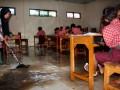 Guru SD Negeri Lopangdomba, Kota Serang, Banten mengepel lantai kelas yang kebanjiran dan berlumpur di sela proses belajar mengajar bertepatan dengan peringatan Hari Pendidikan Nasional 2 Mei, Kamis (2/5). Meski Pemda setempat sudah diinstruksikan Mendiknas untuk memperbaiki drainase guna mengatasi banjir namun hingga saat ini tidak ada realisasinya. (ANTARA/Asep Fathulrahman)
