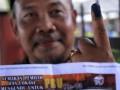 M.M. Maghfur, warga Indonesia yang telah berpindah kewarganegaraan, menunjukkan bukti tinta di jarinya usai memberi suara mereka di sebuah TPS di kawasan Gambok, Kuala Lumpur, Selangor, Malaysia, Minggu (5/5). Malaysia menggelar Pilihan Raya Umum ke-13 yang menjadi ajang bagi Koalisi Barisan Nasional dan Koalisi Pakatan Rakyat bertarung memperebutkan sekitar 13,2 juta suara dari pemilih. (FOTO ANTARA/Fanny Octavianus)