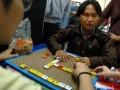 Seorang guru SMP LB jurusan A (Tuna Netra) YPAB Surabaya, Tutus Setyawan (kanan), mencoba alat permainan scrabble, yang dikhususkan untuk penyandang tuna netra, dinamakan Formula Braible, saat kegiatan Pameran Karya Kreatif Alat Permainan Aman dan Menyenangkan di Universitas Surabaya (Ubaya), Rabu (8/5). Pameran yang digelar mahasiswa Teknik Industri Ubaya tersebut, bertujuan untuk mengasah kreativitas mahasiswa, dalam menciptakan alat permainan yang aman dan menyenangkan bagi anak-anak serta penyandang difabel. (FOTO ANTARA/Eric Ireng)