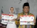 Calon Bupati Lumajang Ali Mudhori bersama isteri memperlihatkan surat suara pada Pilkada Lumajang di TPS 11 Tompokersan, Lumajang, Jawa Timur, Rabu (29/5). Pilkada Lumajang diikuti empat pasang Calon Bupati, yaitu Sjahrazad Masdar - As'at Malik (SAAT), Agus Wicaksono - Adnan Syarif (Arif), Ali Mudhori - Samsul Hadi (ASA) dan Indah Pakarti - Abdul Kafi (Indah - Kafi) yang memperebutkan 819.872 pemilih di 1.872 TPS. (ANTARA FOTO/Seno)