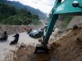 Pengguna jalan melintasi badan jalan yang sedang dibersihkan dengan menggunakan alat berat karena ditutupi longsor di lintasan Bireuen - Takengon pengunungan Singah Mata, Desa Paya Tumpi, kec. Kebayakan Kab. Aceh Tengah, Minggu (7/7). Hingga hari keenam korban gempa tektonik di Kabupaten Aceh Tengah dan Bener Meriah berjumlah 38 orang, enam masih tertimbun longsor, ratusan luka-luka dan ribuan bangunan rusak besar. (ANTARA FOTO/Irwansyah Putra)